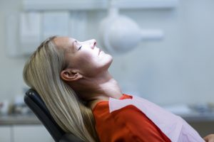 Blonde-haired woman relaxing in a dental chair after receiving sedation